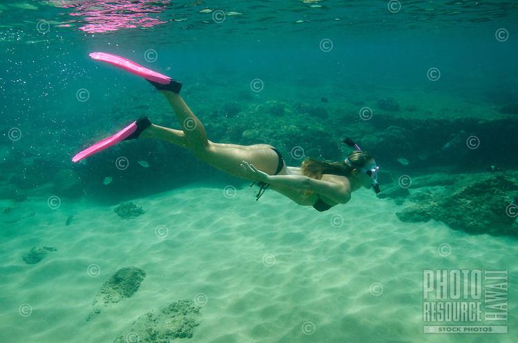 A healthy, fit woman snorkels at Napili Bay, Maui.