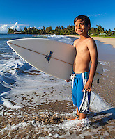 A young local surfer about to head into the ocean at Hanalei Beach, Kaua'i.