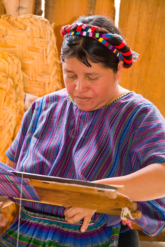 Woman at loom weaving artwork fabrics by hand in colorful dressin San Antonio on remote Lake Atitlan in Guatemal
