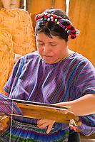 Woman at loom weaving artwork fabrics by hand in colorful dressin San Antonio on remote Lake Atitlan in Guatemal