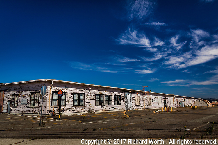 A bright blue sky with wispy clouds over deteriorating building with peeling paint at the former Naval Air Station Alameda.  A building in transition in the process of, being 'repurposed'.