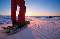 The winter sun sets as a snowshoer pauses while recreating in the Brooks Range, Arctic, Alaska