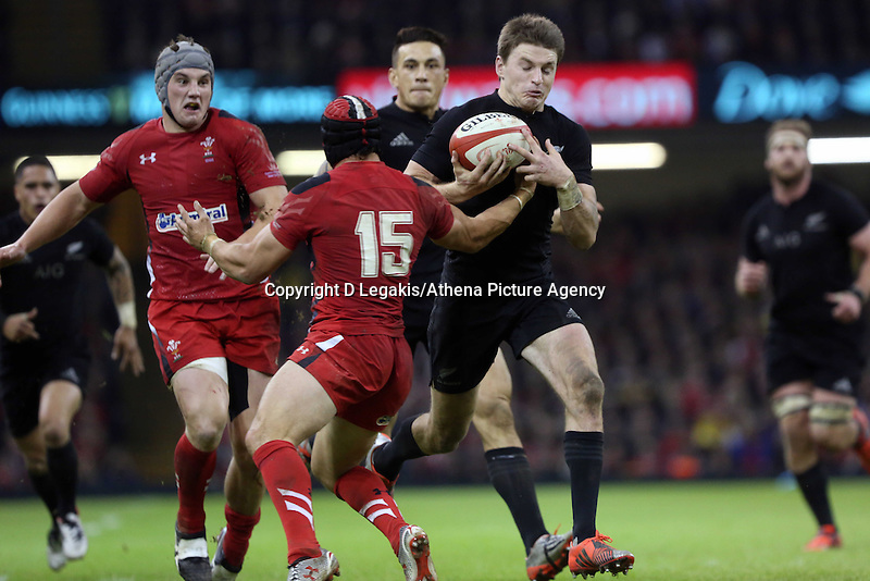 Pictured: Beauden Barrett of New Zealand (R) avoids a tackle by Leigh Halfpenny of Wales (15) to score yet another try for his team Saturday 22 November 2014<br /> Re: Dove Men Series 2014 rugby, Wales v New Zealand at the Millennium Stadium, Cardiff, south Wales, UK.