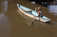 An Indonesian man paddles down a canal in central Jakarta. The city's drainage was built by the Dutch during colonial times however many of them have fallen into disrepair and are clogged with refuse.