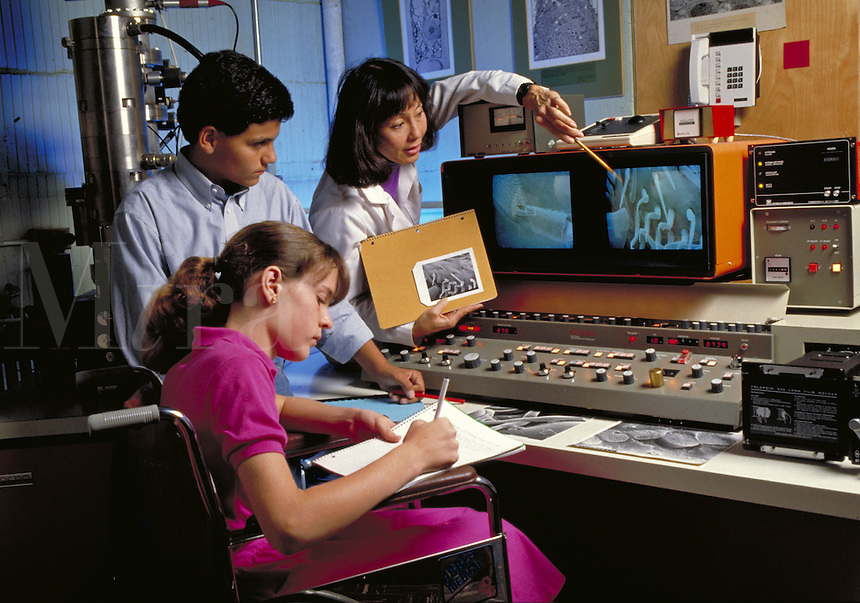 MIDDLE SCHOOL STUDENTS WITH SCANNING ELECTRON MICROSCOPE TECHNICIAN AT UNIVERSITY OF CALIFORNIA SEM WITH IMAGE OF BEE'S KNEE ON SCREEN. SEM TECHNICIAN AND PUPILS. BERKELEY CALIFORNIA, UNIVERSITY OF CALIFORNIA.