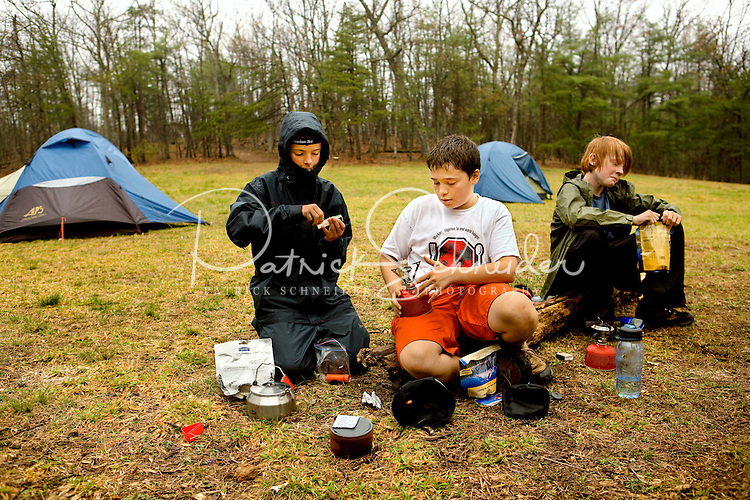 Troop 10 Boy Scouts relax while making a meal during a spring backpacking in the South Mountains State Park in Connelly Springs, North Carolina.