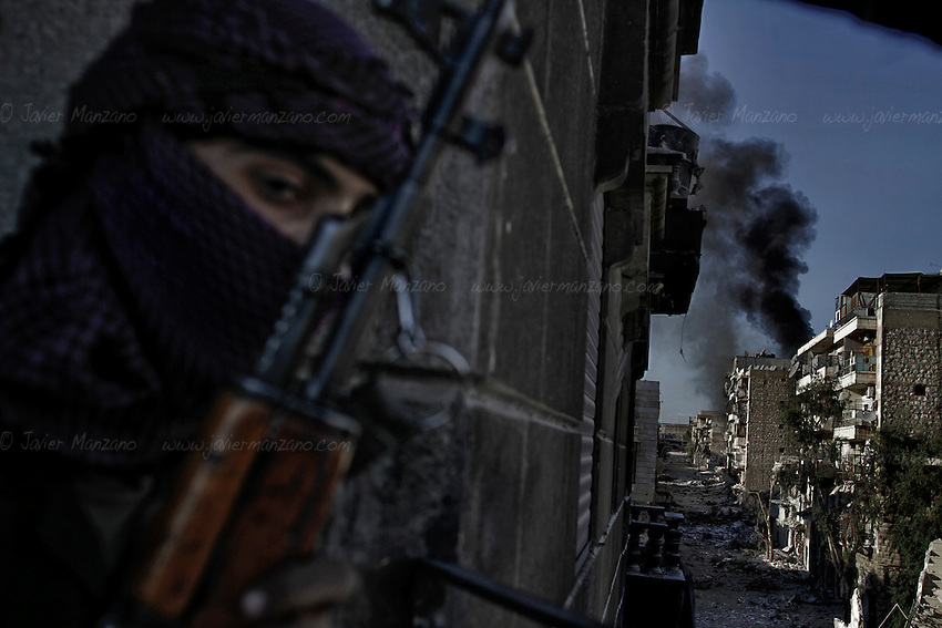 A Free Syria Army soldier looks at the effects of an RPG fired by a rebel soldier on a house allegedly populated by regime loyalists at the heavily contested neighborhood of Karmal Jabl in central Aleppo. This neighborhood has become one of the most contested flash points in the city due to it's proximity to a main road that connects the city from East to West. House-to-house combat has become the norm in this neighborhood as most of it's civilian population has fled. .October 18, 2012...© Javier Manzano..