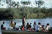 Xingu, Brazil. Posto Leonardo; group of Indian men, women and children in a boat.