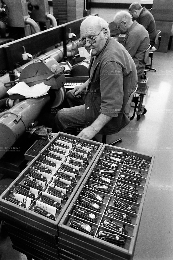 """Switzerland. Canton Jura. Delémont. Wenger factory. Production of Swiss army knifes. Workers at work. in 1992, the man was still allowed to smoke  a cigarette inside while working. Wenger is one of two companies that have manufactured Swiss Army knives. Based in Delémont, Wenger was acquired by rival Victorinox in 2005. Since 2013, Wenger Swiss Army knives are integrated in the Victorinox collection (as the """"Delémont collection""""). © 1992 Didier Ruef"""