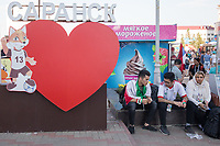 """SARANSK, RUSSIA - June 25, 2018: Some Iran fans sit next to a """"I love Saransk"""" in Millennium Square in Saransk before the 2018 FIFA World Cup group stage match between Iran and Portugal at Mordovia Arena."""