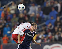 New York Red Bulls forward Andre Akpan (15) and New England Revolution substitute midfielder Andy Dorman (12) battle for head ball. In a Major League Soccer (MLS) match, the New England Revolution (blue) tied New York Red Bulls (white), 1-1, at Gillette Stadium on May 11, 2013.