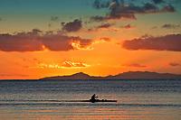 Sunset over Taha'a and Raiatea islands with a man paddling in a canoe, on Huahine island, near Tahiti, French Polynesia, Pacific Ocean
