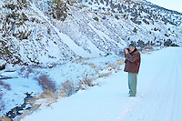 Person taking picture of snowfall in stream. Near Adel, Oregon