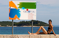 A young woman in bikini looking at the camera on a wall, a sign saying Welcome to Croatia, on the beach by the blue sea, and island in the background Orebic town, holiday resort on the south coast of the Peljesac peninsula. Orebic town. Peljesac peninsula. Dalmatian Coast, Croatia, Europe.