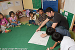 Education preschool 3-5 year olds male teacher working with group during circle time, writing on chart paper, activity