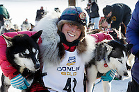 Lisbet Norris poses with her lead dogs at the finish line in Nome on Saturday March 21, 2015 during Iditarod 2015.  <br /> <br /> (C) Jeff Schultz/SchultzPhoto.com - ALL RIGHTS RESERVED<br />  DUPLICATION  PROHIBITED  WITHOUT  PERMISSION