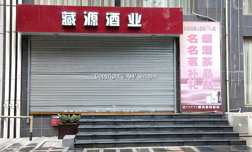 """A shop that collects authentic empty bottles of high end wine, Guangzhou, Guangdong Province, China, 18 July 2014. The Chinese sign above the shop reads in English, """"Hidden Source Liquor Industry"""". Collected empty bottles are often recycled into the Chinese underground fake wine industry.<br /> <br /> PHOTO BY SINOPIX"""