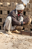 Rajasthan, India.  Man Placing Mud in Brick Mold.