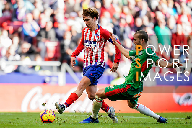 Antoine Griezmann of Atletico de Madrid (L) is tackled by Victor Laguardia Cisneros of Deportivo Alaves during the La Liga 2018-19 match between Atletico de Madrid and Deportivo Alaves at Wanda Metropolitano on December 08 2018 in Madrid, Spain. Photo by Diego Souto / Power Sport Images
