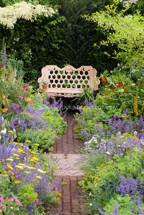 Wrought iron Garden bench in lush springtime flower garden with purple Lupinus lupines, iris, peonies paeonia, Allium, Nepeta catmints, Fritillaria imperalis fritillaries bulbs, in soft pastel colors of blue and lavender, trees and shrubs, brick pathway, romance and beautiful