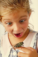 Young girl with Cicada insect on her hand--funny expression.