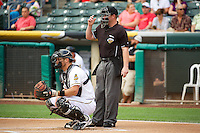John Hester (22) of the Salt Lake Bees behind the plate with home plate umpire Nick Bailey as the Bees faced the Tacoma Rainiers at Smith's Ballpark on July 9, 2014 in Salt Lake City, Utah.  (Stephen Smith/Four Seam Images)