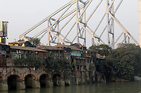 The Howrah bridge looms over a community and the Ganges River in Kolkata.<br /> <br /> To license this image, please contact the National Geographic Creative Collection:<br /> <br /> Image ID: 1925779 <br />  <br /> Email: natgeocreative@ngs.org<br /> <br /> Telephone: 202 857 7537 / Toll Free 800 434 2244<br /> <br /> National Geographic Creative<br /> 1145 17th St NW, Washington DC 20036