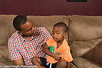 Three year old boy at home sitting with father on couch talking problem difficulty