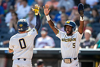 Michigan Wolverines outfielder Christian Bullock (5) celebrates with teammate Joe Donovan (0) after scoring against the Texas Tech Red Raiders in the NCAA College World Series on June 21, 2019 at TD Ameritrade Park in Omaha, Nebraska. Michigan defeated Texas Tech 15-3 and will play in the CWS Finals. (Andrew Woolley/Four Seam Images)