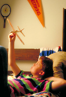 Young male child playing with a toy airplane, using imagination to pretend that he is an airplane pilot, in his room. boy. Houston Texas.