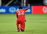 LAKE BUENA VISTA, FL - JULY 26: Richie Laryea of Toronto FC kneels and raises his fist during a game between New York City FC and Toronto FC at ESPN Wide World of Sports on July 26, 2020 in Lake Buena Vista, Florida.