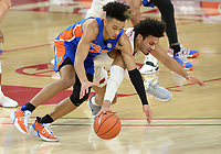 Florida guard Tre Mann (left) and Arkansas guard Justin Smith (right) reach Tuesday, Feb. 16, 2021, for a loose ball during the first half of play in Bud Walton Arena. Visit nwaonline.com/210217Daily/ for today's photo gallery. <br /> (NWA Democrat-Gazette/Andy Shupe)