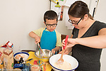 3 year old boy at home with his mother in kitchen, helping her cook, baking, stirring ingredients in bowls for cornbread