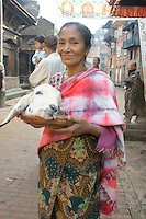 woman with head of a sacrificed goat during dashein festival time in Bhaktapur, Nepal. October 2011.Newar culture is famous for blending Hindu and tantric buddhist tradtions in Nepal, also rooted in earlier animistic tradtions, as both Hindu and Buddhist culture do in parts - as can be seen in archaic rituals of Dashein sacrifices for goddess Durga and her nine incarnations.