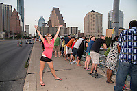 Cheerful attractive Austin tourist waves with excitement and joy while waiting for the bats to take flight on the Congress Ave. Bat Bridge in downtown Austin, Texas.