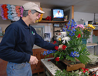 Florist David Feola in Buckhannon, WV, prepares an arrangement Friday, Jan. 6, 2006, for a funeral service for one of the miners killed in a mine explosion Monday at a mine in Sago as a television news report talks about the status of the only surviving miner whop's in a Pittsburgh, Pa. hospital. Twelve miners died in the explosion. (Photo by Gary Gardiner)<br />