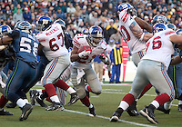 New York Giants running back Tiki Barber cuts up field through a hole created by his offensive line in the fourth quarter against the Seattle Seahawks  at Quest Field in Seattle, WA.