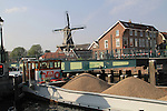 The De Adriaan Windmill Museum and barge on the Spaarne River, Haarlem, Holland, Netherlands.