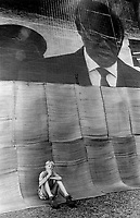 A boy sits beneath a big screen showing the inauguration of Nelson Mandela as President.
