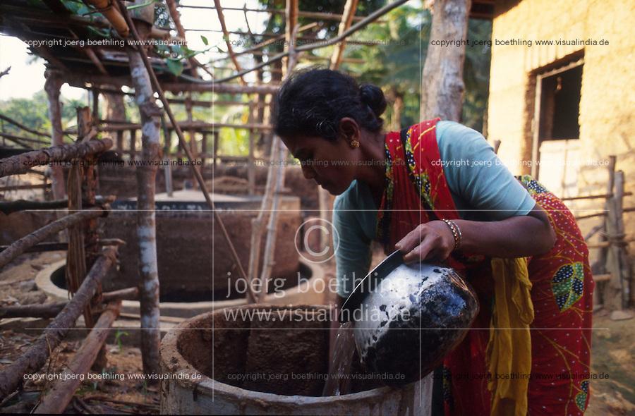 INDIA Karnataka Taccode, woman with biogas plant, the biogas is used for cooking in the kitchen to safe fire woods / INDIEN Frau befuellt eine kleine Biogasanlage, das Biogas wird in der Kueche zum kochen genutzt und spart Feuerholz ein