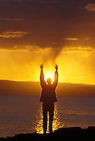 woman raising her arms to worship the setting sun in the San Juan Islands of Washington