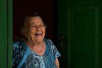 """Rita Gregório, 91 anos, matriarca e esposa do Padrinho Sebastião, um dos principais fundadores da doutrina e da comunidade. <br /> <br /> O Santo Daime, bebida sagrada para a doutrina, encontra suas origens nas populações indígenas da Amazônia ocidental, iniciando como movimento doutrinário nas primeiras décadas do século XX, por meio do trabalho espiritual do seu fundador, o maranhense e neto de escravos Raimundo Irineu Serra. Segundo os registros, ao Mestre Irineu foi revelada uma doutrina de cunho cristão e eclético, reunindo tradições católicas, espíritas, esotéricas, caboclas e indígenas em torno do uso ritual do milenar chá conhecido pelos povos Incas como ayahuasca - vinho das almas - e por ele denominado Santo Daime"""". <br /> Acre, Brasil<br /> Foto Eraldo Peres/Photoagência/Acervo H<br /> 2016<br /> <br /> Vila Céu do Mapiá<br /> A vila Céu do Mapiá, fundada 1983, está situada nas cabeceiras do igarapé Mapiá, distando 30 km do Rio Purus, numa das áreas mais preservadas da Amazônia ocidental brasileira. Só é acessível por meio fluvial, descendo o Rio Purus e depois subindo o igarapé Mapiá por no mínimo seis horas. Nos primeiros tempos a subida do igarapé por canoa podia levar mais de um dia, dificultada pela grande quantidade de troncos caídos sobre se leito, devido à décadas de completo abandono."""