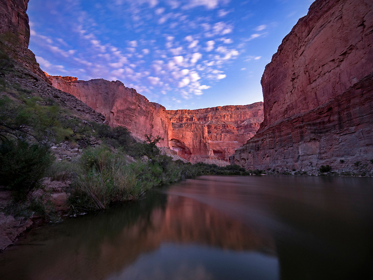 The cliffs along the Colorado River as viewed from Saddle Canyon Camp glow at sunrise in the Grand Canyon National Park, AZ