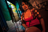 A Salvadoran sex worker sits in front of a room where her sexual services are offered to clients in San Salvador, El Salvador, 15 February 2014. Although prostitution is not legal in El Salvador, dozens of street sex workers, wearing provocative miniskirts, hang out in the dirty streets close to the capital's historic center. Sex workers of all ages are seen on the streets but a significant part of them are single mothers abandoned by their male partners. Due to the absence of state social programs, they often seek solutions to their economic problems in sex work. The environment of street sex business is strongly competitive and dangerous, closely tied to the criminal networks (street gangs) that demand extortion payments. Therefore, sex workers employ any tool at their disposal to struggle hard, either with their fellow workers, with violent clients or with gang members who operate in the harsh world of street prostitution.