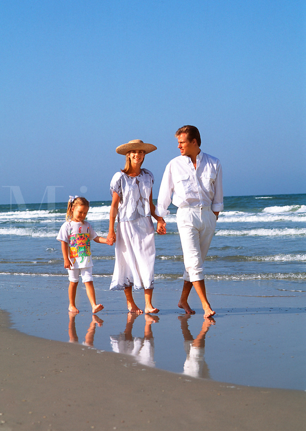 Young family in white clothes walking on beach