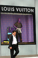 People pass a Louis Vuitton store in down-town Shanghai. .23 Apr 2005