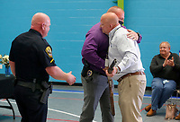 Retiring city of Rogers police chief Hayes Minor (from right) receives a hug from detective Rick Yager after receiving an engraved Beretta Over and Under 12 gauge shotgun from David Crawford, president of the Rogers Fraternal Order of Police Wednesday, April 28, 2021, during a retirement reception in his honor at the Rogers Activity Center. Hayes served 27 years in law enforcement with the city and the last six as the police chief for the department. Check out nwaonline.com/210429Daily/ and nwadg.com/photos for a photo gallery.<br /> (NWA Democrat-Gazette/David Gottschalk)