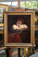 BNPS.co.uk (01202 558833)<br /> Pic: MaxWillcock/BNPS<br /> <br /> Pictured: Hannah Farthing, Paintings Department Assistant at Woolley and Wallis, with 'The Laughing Girl' by Sir Joshua Reynolds.<br /> <br /> A 'lost' painting by famed artist Sir Joshua Reynolds that had not been seen for 84 years has sold for £44,000 following a bidding war.<br /> <br /> The oil painting was discovered hanging on the stairwell wall of a private family home in Hampshire during a routine valuation.<br /> <br /> The owners, who inherited the painting, had believed it was a copy and were stunned to be told it was by the 18th century painter.