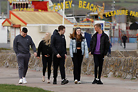Pictured: People go for a walk, not observing social distancing, by Coney beach in Porthcawl, Wales, UK. <br /> Re: Covid-19 Coronavirus pandemic, UK.