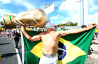 A Brazil supporter wearing a wrestling mask kisses a giant replica World Cup trophy